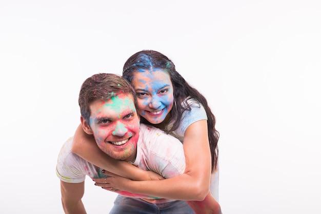 Vakantie, holi en mensen concept - gelukkige paar plezier bedekt met verf op witte muur