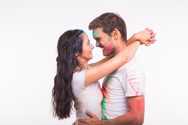 Vakantie, holi en mensen concept - gelukkige paar plezier met veelkleurige poeder op hun gezichten op wit oppervlak