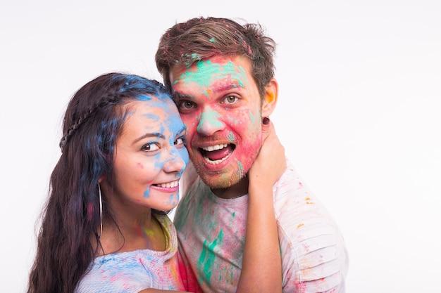 Vakantie, holi en mensen concept - lachende grappige vrouw en man poseren met veelkleurige poeder op hun gezichten op wit oppervlak
