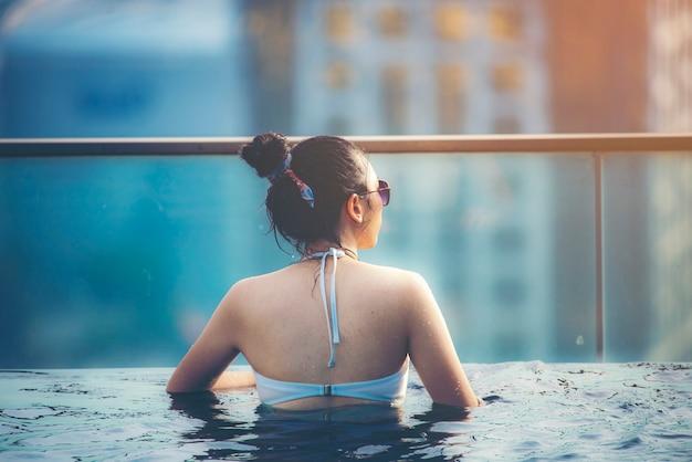 Vakantie in kuala-lumpur. de jonge vrouw geniet van zwemmend in dak hoogste pool met mooie stadsmening