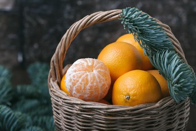 Vakantie-inhoud, mandarijnen, gepelde mandarijn in een rieten mand, vintage, vuren tak, close-up, donkerbruine achtergrond, horizontaal