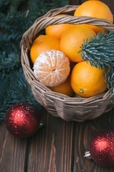 Vakantie-inhoud, mandarijnen, gepelde mandarijn in een rieten mand, vintage, vuren tak, kerstboom rode ballen, donkerbruine achtergrond, bovenaanzicht