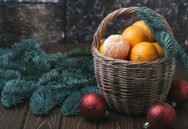 Vakantie-inhoud, mandarijnen, gepelde mandarijn in een rieten mand, vintage, vuren tak, kerstboom rode ballen, donkerbruine achtergrond, horizontaal
