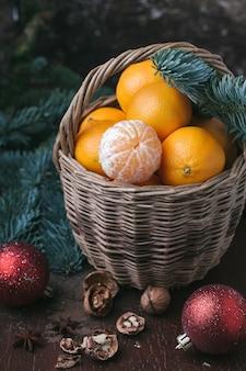 Vakantie-inhoud, mandarijnen, gepelde mandarijn in een rieten mand, vintage, vuren tak, kerstboom rode ballen, walnoot, donkerbruine achtergrond