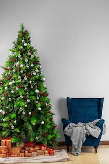 Vakantie interieur, mooi versierde kerstboom met blauwe fauteuil