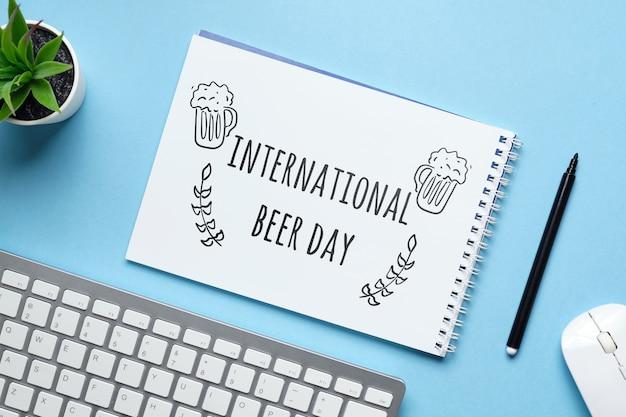 Vakantie internationale bierdag getekend op een notitieboekje.