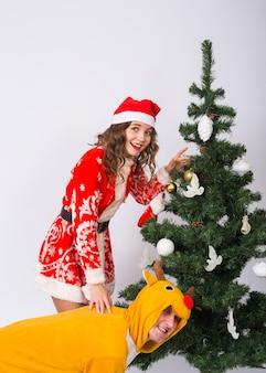 Vakantie-, kerst- en grapconcept - grappige man in hertenkostuum en vrouw in kerstman-kostuum zijn gek rond in de buurt van de kerstboom.