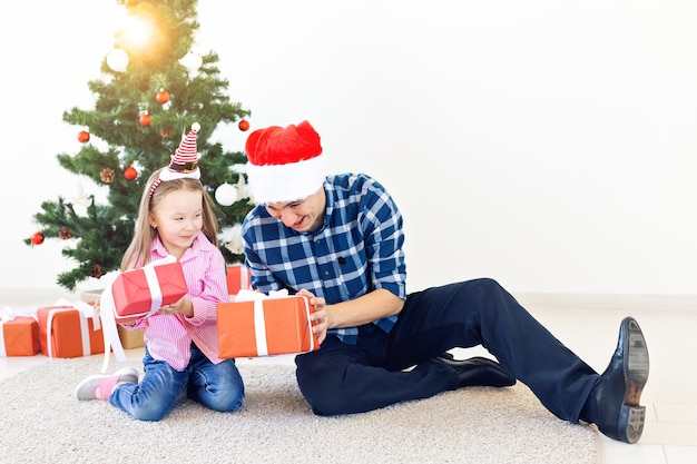 Vakantie, kerst, familie en geluk concept - close-up van vader en dochter met geschenkdoos