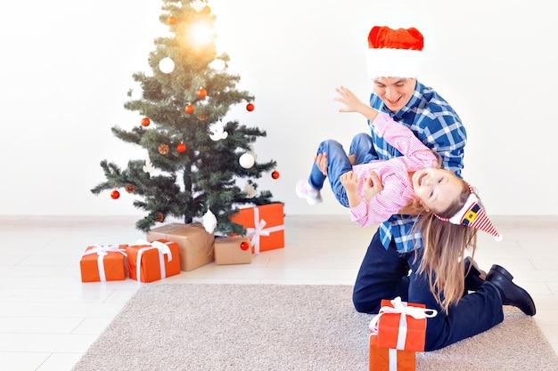 Vakantie, kerst, familie en geluk concept - grappige vader en dochter in de buurt van kerstboom
