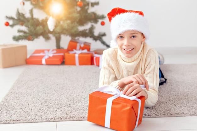 Vakantie, kerstmis, jeugd en mensen concept - lachende gelukkige tiener jongen in kerstmuts opent geschenkdoos over kerstboom achtergrond.