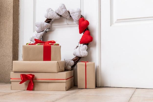 Vakantie krans met hartjes en winkel versierde dozen op de verdieping in de buurt van witte deur