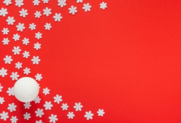 Vakantie lichte achtergrond, witte sneeuwvlokken en kerstbal op rode achtergrond, prettige kerstdagen en gelukkig nieuwjaar concept, plat leggen, bovenaanzicht, kopie ruimte