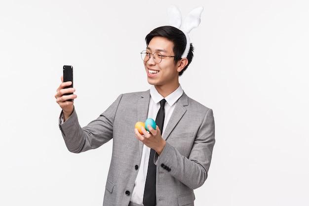 Vakantie, mensen en feest concept. taille-up portret van jonge gelukkige en dwaze aziatische man in pak, draagt konijnenoren, neemt selfie met beschilderde eieren als paasdag vieren, op een witte muur