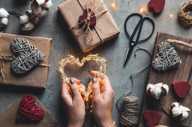 Vakantie, mensen en viering concept - close-up van vrouw valentijn versieren presenteert