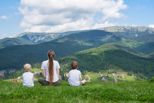 Vakantie met het gezin. moeder en twee zonen bewonderen het uitzicht op de berg.