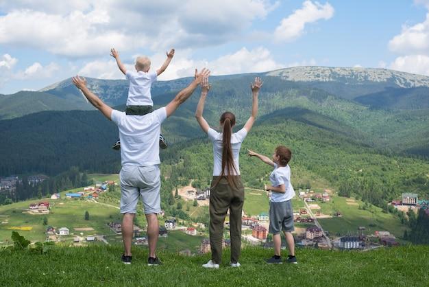 Vakantie met het gezin. ouders en kinderen staan met hun handen omhoog. bergen op de achtergrond. achteraanzicht