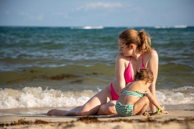 Vakantie met kinderen moeder en baby spelen in het zand aan de kust