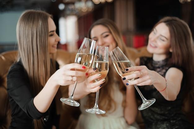 Vakantie, nachtleven, vrijgezellenfeest en mensen concept. glimlachende vrouwen met champagneglazen.
