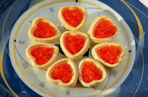 Vakantie new year's snack hartvormige taartjes met rode kaviaar op een bord met een wijzerplaat