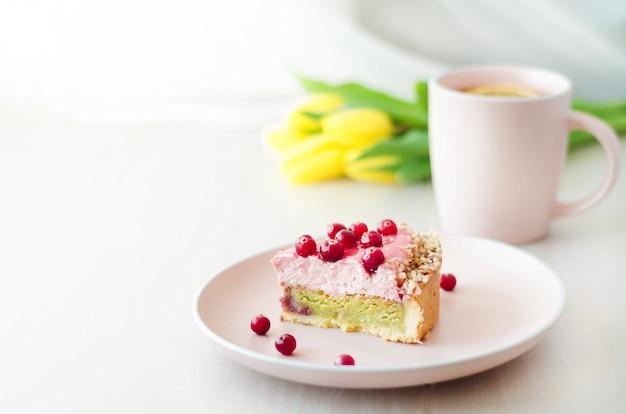 Vakantie ochtend, ontbijt met gele bloemen tulpen, cake, thee in roze mok op lichte ondergrond.