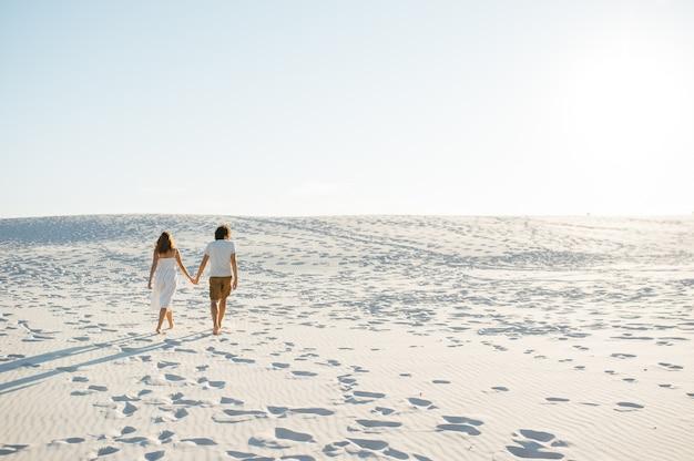 Vakantie paar wandelen op strand samen verliefd houden om elkaar heen. gelukkig interraciaal jong koppel.