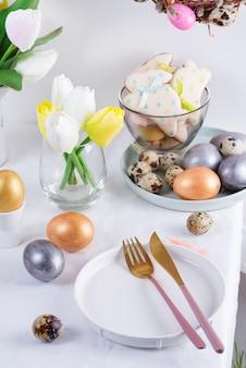 Vakantie pasen tabel instelling met ambachtelijke beschilderde eieren, gebakken koekjes en verse bloemen op een tafel bedekt witte doek.