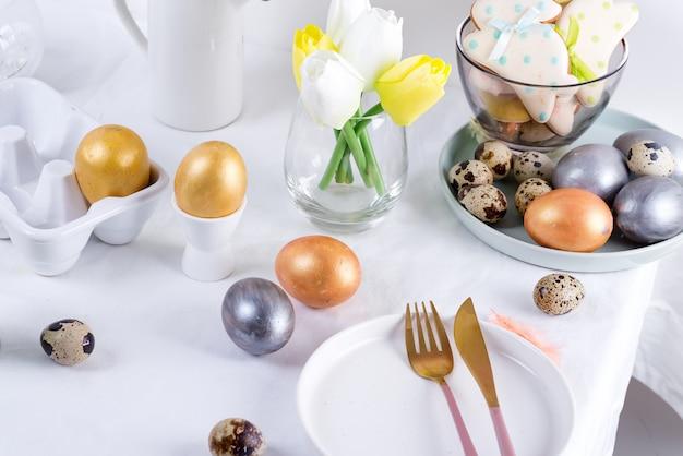 Vakantie pasen tafel satteing met ambachtelijke beschilderde eieren, gebakken koekjes en verse bloemen op een tafel bedekt witte doek.