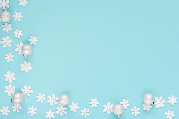 Vakantie pastel achtergrond, witte sneeuwvlokken en kerstbal op een zacht blauw