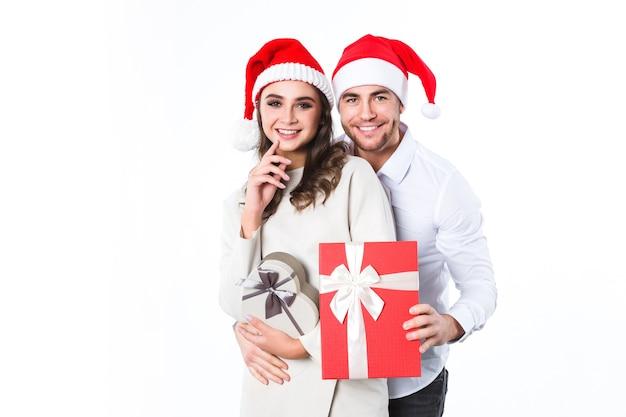 Vakantie. portret van aantrekkelijk jong paar in santahoeden met gift