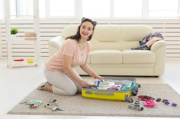 Vakantie-, reis- en reisconcept - jonge vrouw pakt een koffer thuis in de slaapkamer, veel