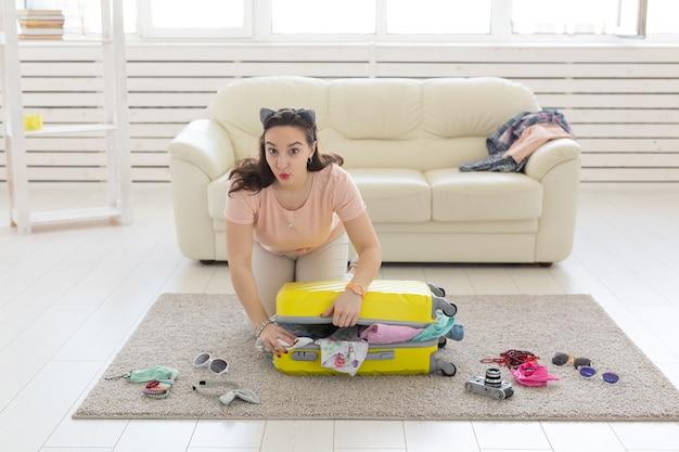 Vakantie-, reis- en reisconcept - jonge vrouw verzamelt thuis veel een koffer in de slaapkamer