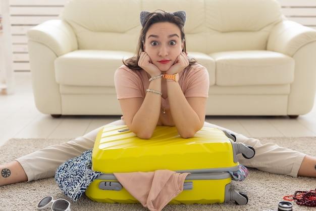Vakantie, reis en reisconcept - vrouw verzamelt thuis een gele koffer