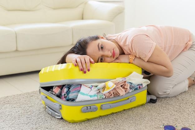 Vakantie-, reis- en vakantieconcept - vrouw die koffer met veel dingen probeert te sluiten