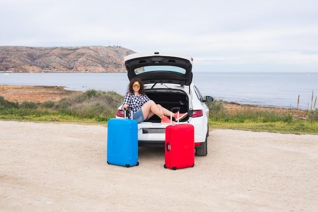 Vakantie, reizen en toerisme concept - jonge vrouw met koffers op autorit.