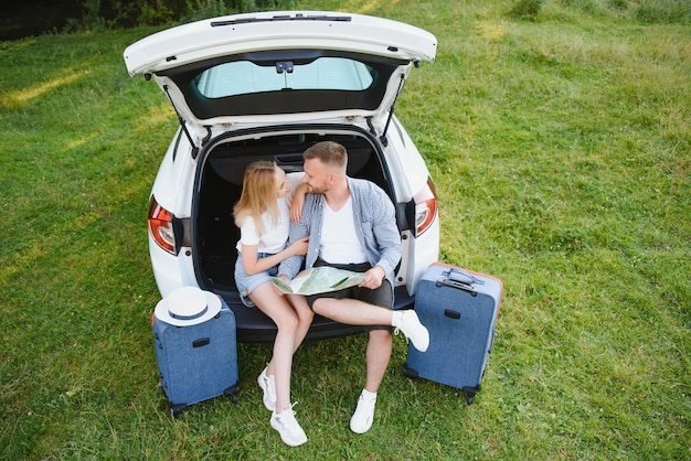 Vakantie, reizen - familie klaar voor de reis voor de zomervakantie. koffers en autoroute. mensen met een kaart in handen die een roadtrip plannen. reisconcept. reiziger.
