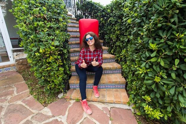 Vakantie, reizen, mensen concept. jonge vrouw in zonnebril zittend op trappen met koffers en glimlachen.