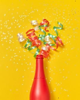 Vakantie rood geschilderde wijnfles met veelkleurige papieren srirals als champagne bubbels op een gele achtergrond, kopieer ruimte. plat leggen.