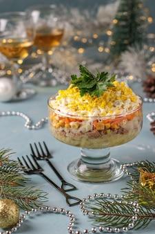 Vakantie salade met ingeblikte vis, eieren, wortelen en aardappelen, traditionele russische gerechten, close-up, verticale oriëntatie