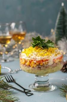 Vakantie salade met ingeblikte vis, eieren, wortelen en aardappelen, traditionele russische gerechten, close-up