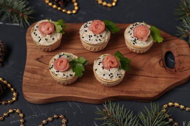 Vakantie taartjes met kaas, zalm en avocado op houten bord op donkere ondergrond, close-up, horizontale oriëntatie