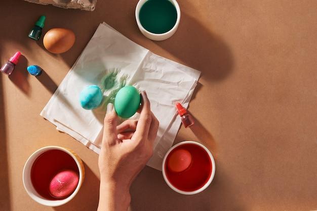 Vakantie, traditie en mensenconcept - close-up van mensenhanden die paaseieren kleuren met borstel -