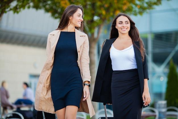 Vakantie, twee gelukkige meisjes die samen naar het buitenland reizen, kofferbagage op de luchthaven dragen