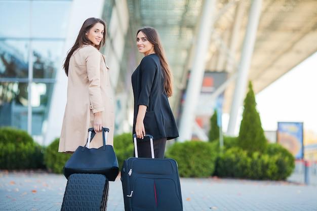 Vakantie. twee stijlvolle vrouwelijke reizigers lopen met hun bagage in de luchthaven