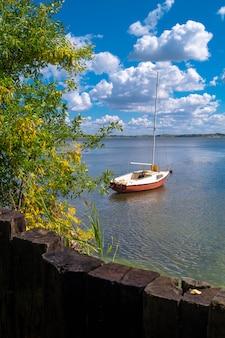 Vakantie vakantie reizen concept: zeilboot jacht op rivier naast de kust in de zomer op bewolkte hemel