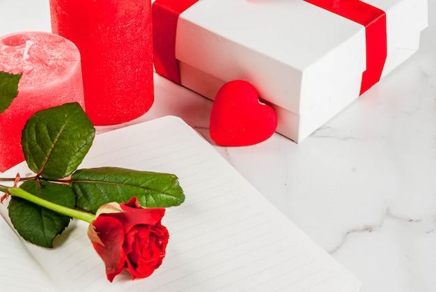 Vakantie, valentijnsdag. boeket rode rozen, stropdas met een rood lint, met blocnote, gewikkelde geschenkdoos en rode kaars. op een witte marmeren tafel, copyspace bovenaanzicht