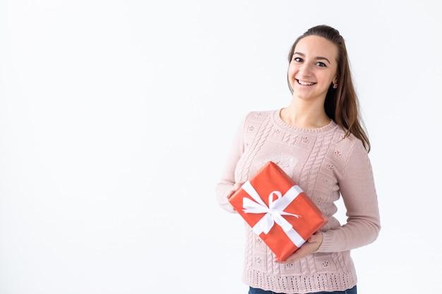 Vakantie, valentijnsdag en feestelijk concept - mooie glimlachende vrouw met lang haar met geschenkdoos.