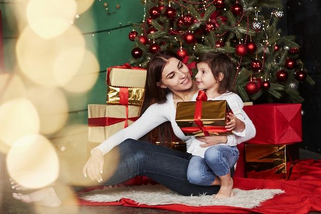Vakantie verenigt mensen. vrolijke moeder en dochter zitten in de buurt van de kerstboom die erachter. leuk portret