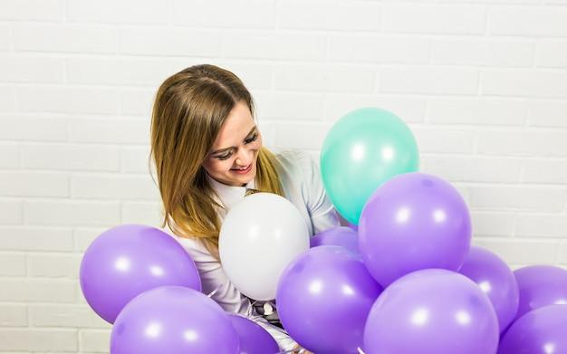 Vakantie, viering en levensstijl concept - mooie vrouw met kleurrijke ballonnen binnenshuis