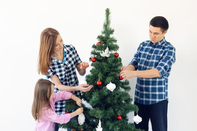 Vakantie, x-mas en vieren concept - gelukkige familie kerstboom versieren in vakantie op witte achtergrond.