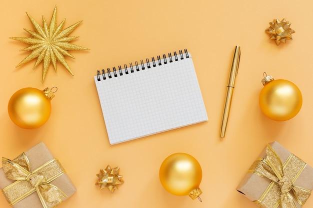 Vakantieachtergrond, gouden achtergrond met glitter gouden ster en geschenkdozen en kerstballen, open spiraalvormige blocnote en pen, plat leggen, bovenaanzicht, kopie ruimte